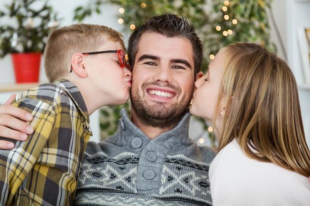 Fils et fille embrassant père dans le visage