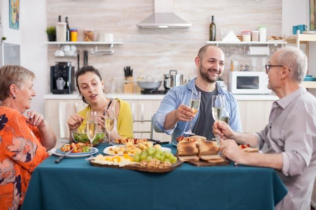Fils joyeux regardant père tenant un verre de vin pendant le brunch familial. mère et fille regardant smartphone. pommes de terre assaisonnées savoureuses.