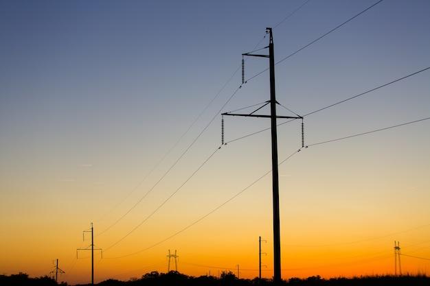 Fils sur les lignes électriques entrant dans le coucher du soleil