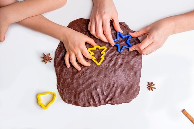 Fils de maman et enfant découpé avec des moules de pâte pour biscuits ou pain d'épice. cuisson de la pâte pour la cuisson de noël.