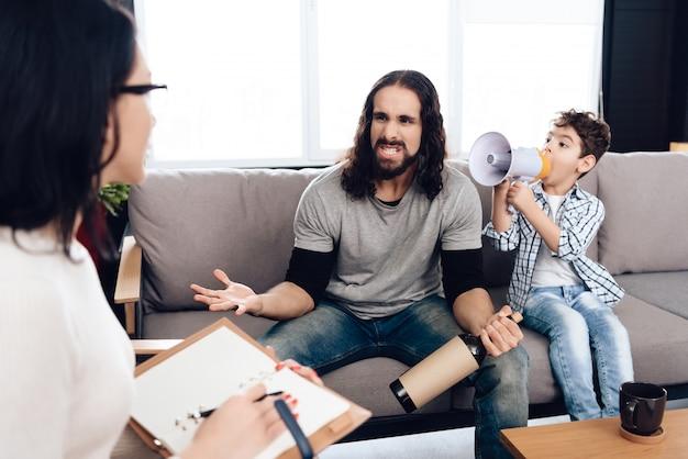 Un fils avec un mégaphone obtient un père dans le bureau d'un psychiatre.