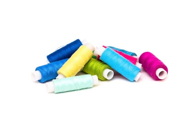 Des fils multicolores sont empilés sur un fond blanc.