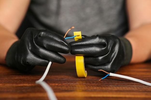 Les fils nus sont isolés avec du ruban adhésif par un homme en gants de travail. connexion de deux fils. photo de haute qualité