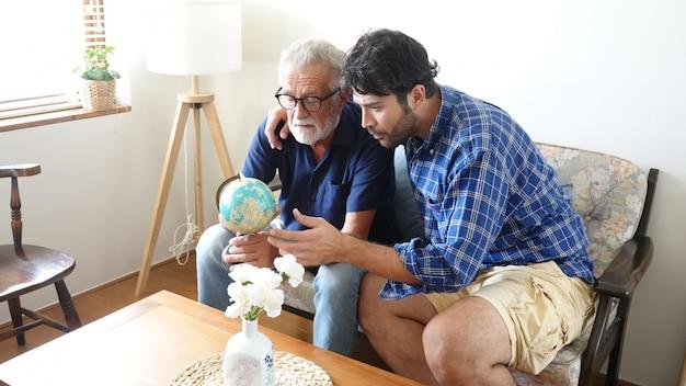 Fils et père aîné regardant la carte globale et gesticulant sur son ensemble dans le salon