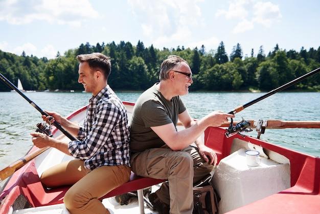 Fils et père avec canne à pêche sur un bateau