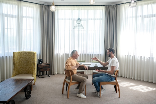 Un fils et un père discutant et prenant le thé ensemble