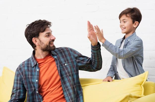 Un fils et un père souriant frappent cinq