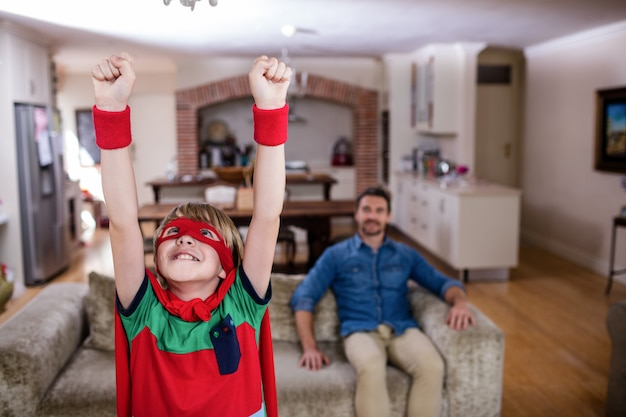 Fils prétendant être un super-héros tandis que le père est assis sur un canapé