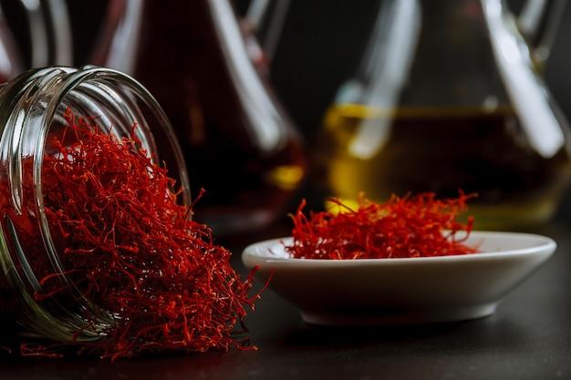 Fils de safran séchés dans une bouteille en verre et extrait d'huile.