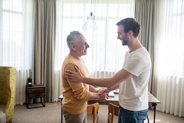 Fils visitant son père, tous les deux semblant heureux