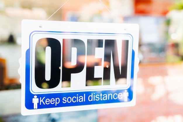 Fin de la mise en quarantaine.nous sommes panneau ouvert sur la porte d'entrée de l'hôtel d'affaires, café, magasin local, propriétaire du service accueillant les clients après une épidémie de coronavirus