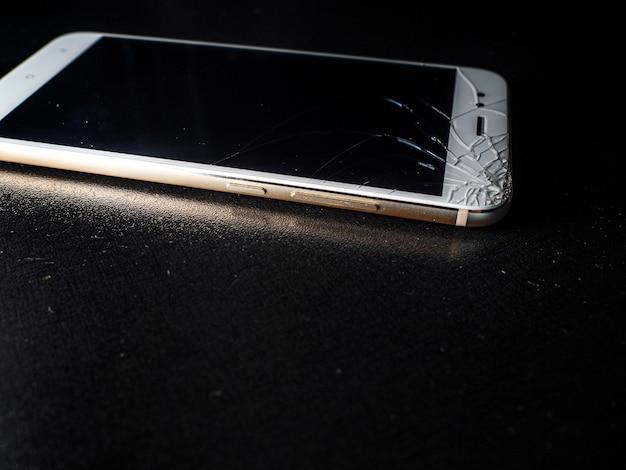 Un fin smartphone blanc avec un écran très fissuré, dommage en cas de chute.