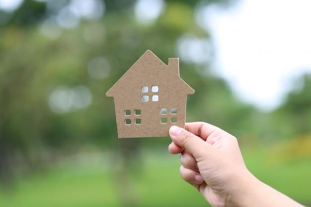 Finance et banque concept, main de femme tenant maison modèle naturel