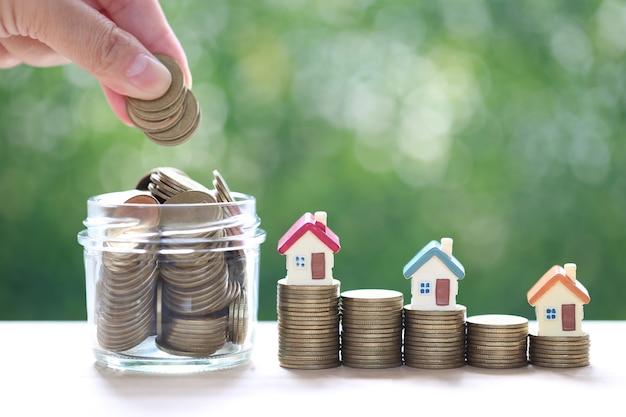 Finance, maison modèle sur pile de pièces d'argent sur fond vert naturel, investissement commercial et immobilier