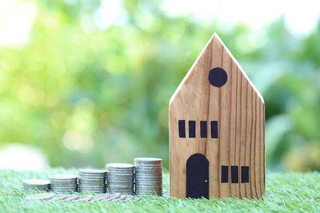 Finance, pile de pièces d'argent et maison modèle sur vert naturel