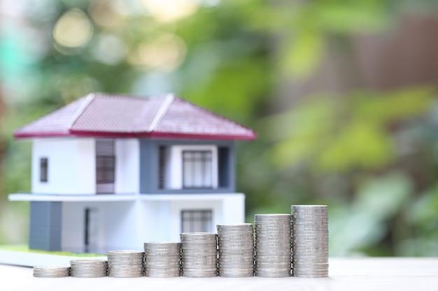 Finance, pile de pièces de monnaie et maison modèle sur vert naturel, investissement commercial et immobilier