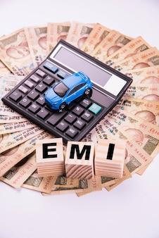 Financement automatique ou prêt en inde - concept montrant le modèle de voiture jouet, les clés, les billets de banque indiens et la calculatrice pour les calculs emi, etc. disposés sur fond clair