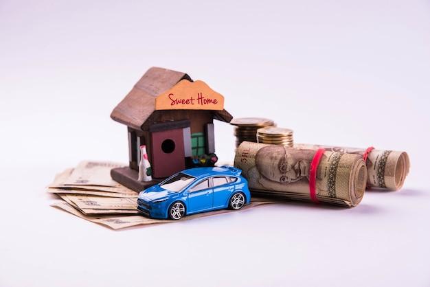 Financement automobile et prêt ou achat de logement en inde - concept montrant un modèle de voiture et de maison en 3d, des clés, des billets de banque indiens et une calculatrice, etc.