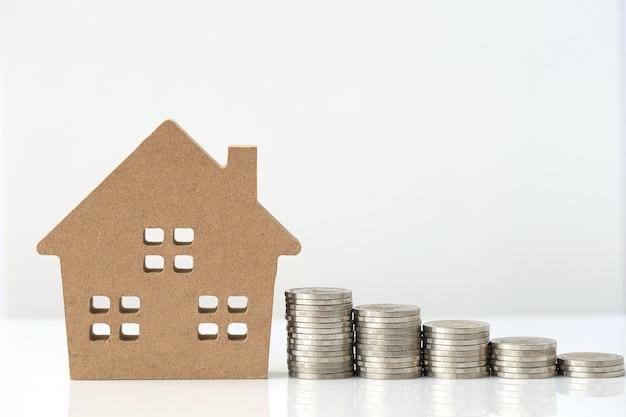 Finances, pile de pièces d'argent et maison modèle sur blanc
