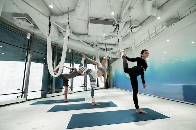Finir le yoga. deux femmes et un homme debout sur une jambe en finissant le yoga avec étirement