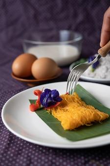 Le fios de ovos sur l'assiette se compose de deux œufs et du lait de coco.