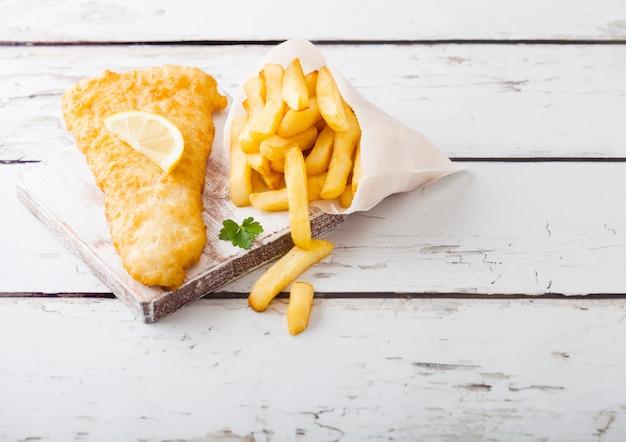 Fish and chips britannique traditionnel avec sauce tartare sur une planche à découper sur une table en bois blanc.