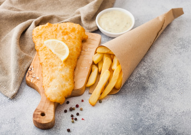 Fish and chips britannique traditionnel avec sauce tartare sur planche à découper sur tableau blanc.