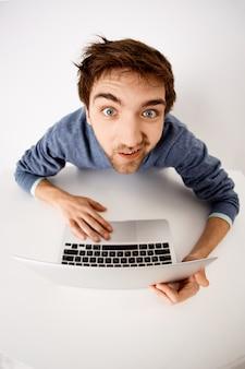 Fish-eye, angle supérieur, coup, de, rigolote, type, dévisager, à, sourire, utilisation ordinateur portable, travail projet, dactylographie ordinateur
