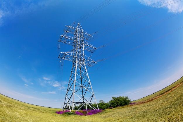 Fish-eye photo de pylônes électriques à haute tension contre le ciel bleu