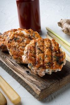 Fishcakes asiatiques rapides grillés à partir de saumon et d'herbes épicées, sur fond texturé blanc