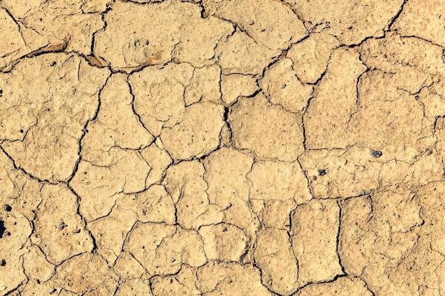 Fissure au sol de la terre avec de la poussière et une texture de surface sèche rugueuse la sécheresse manque d'eau