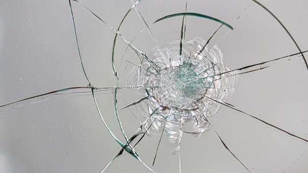 Fissures sur le verre sur une surface blanche