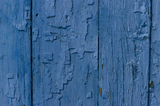 Des fissures de la vieille peinture bleue sur une planche de bois. fond vintage bleu classique.