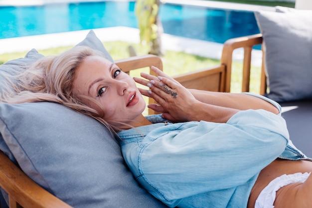 Fit belle femme européenne aux cheveux blonds courts en chemise en jean bleu et culotte de bikini blanc