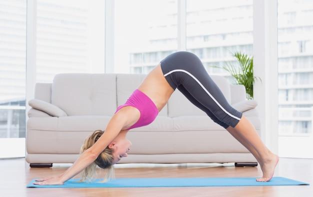 Fit blonde dans la pose de dauphin sur tapis d'exercice