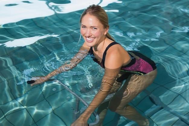 Fit blonde heureuse en utilisant un vélo d'exercice sous-marin