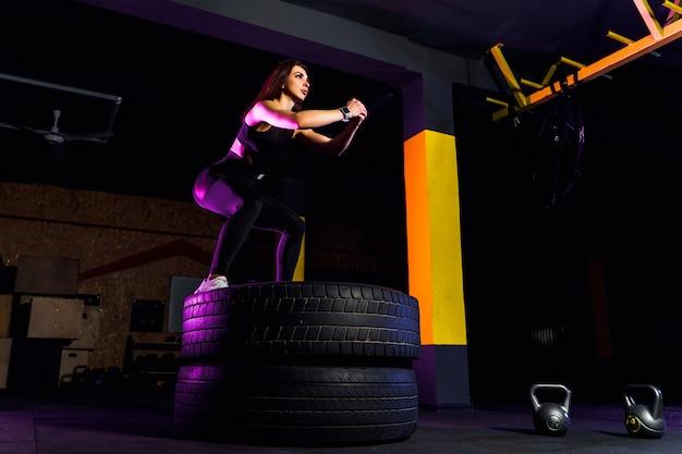 Fit box jeune femme sautant sur les pneus