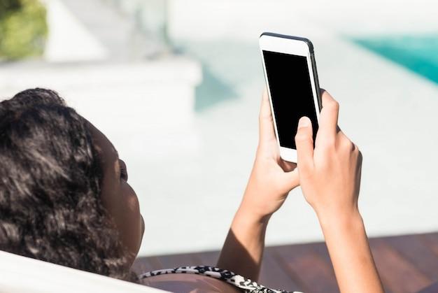 Fit brune allongée sur une chaise longue et utilisant un smartphone au bord de la piscine