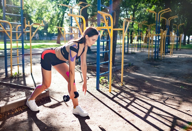 Fit brunette femme magnifique formation à l'aide d'haltères dans le parc et le terrain de sport