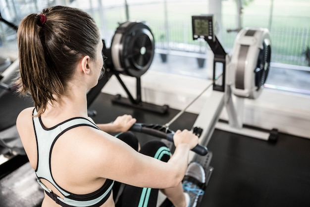 Fit brunette sur machine à dessiner à la gym