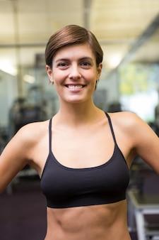 Fit brunette en soutien-gorge de sport noir souriant à la caméra