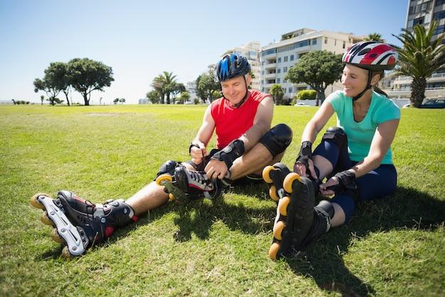 Fit couple d'âge mûr attachant leurs patins à roues alignées sur l'herbe