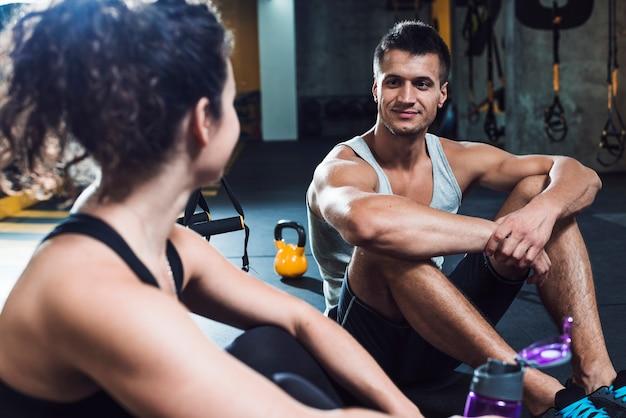 Fit couple assis sur le sol dans la salle de gym