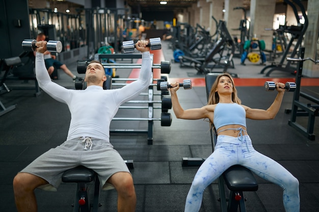 Fit couple faisant de l'exercice avec des haltères dans la salle de sport