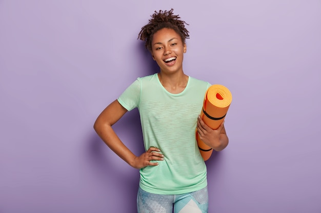 Fit femme afro positive fait des exercices de fitness et d'entraînement à la maison, tient le karemat orange