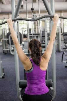 Fit femme à l'aide d'une machine de musculation en salle de sport