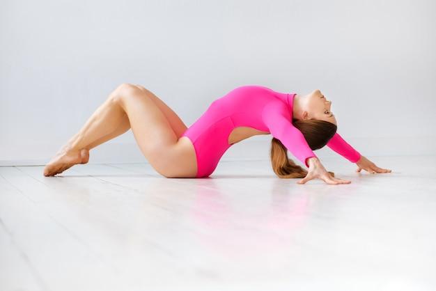 Fit femme athlétique souple dans un justaucorps rose à la mode faisant un étirement du dos sur un plancher en bois blanc