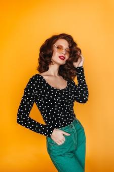 Fit femme au gingembre en pantalon vert regardant la caméra. photo de studio de jolie fille posant avec la main dans la poche.