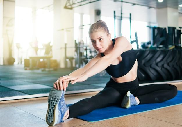 Fit femme blonde faisant étirement sa jambe avant l'exercice alors qu'il était assis sur un tapis dans le gymnase entraînement pré-entraînement