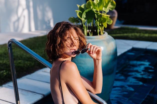 Fit femme brune bronzée en maillot de bain ajusté noir à l'hôtel villa dans la piscine